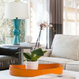 Klasyczna kanapa, fotel w stylu vintage i fikuśna lampka w turkusowym kolorze najlepiej odzwierciedlają różnorodność stylów panującą w domu. Fot. Refined.