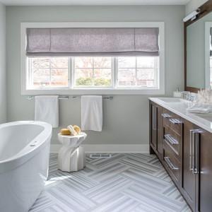 Dominującą w łazience sterylną biel ocieplono drewnianymi meblami. Obecność naturalnego drewna stwarza w pomieszczeniu przytulniejszy klimat. Fot. Refined.