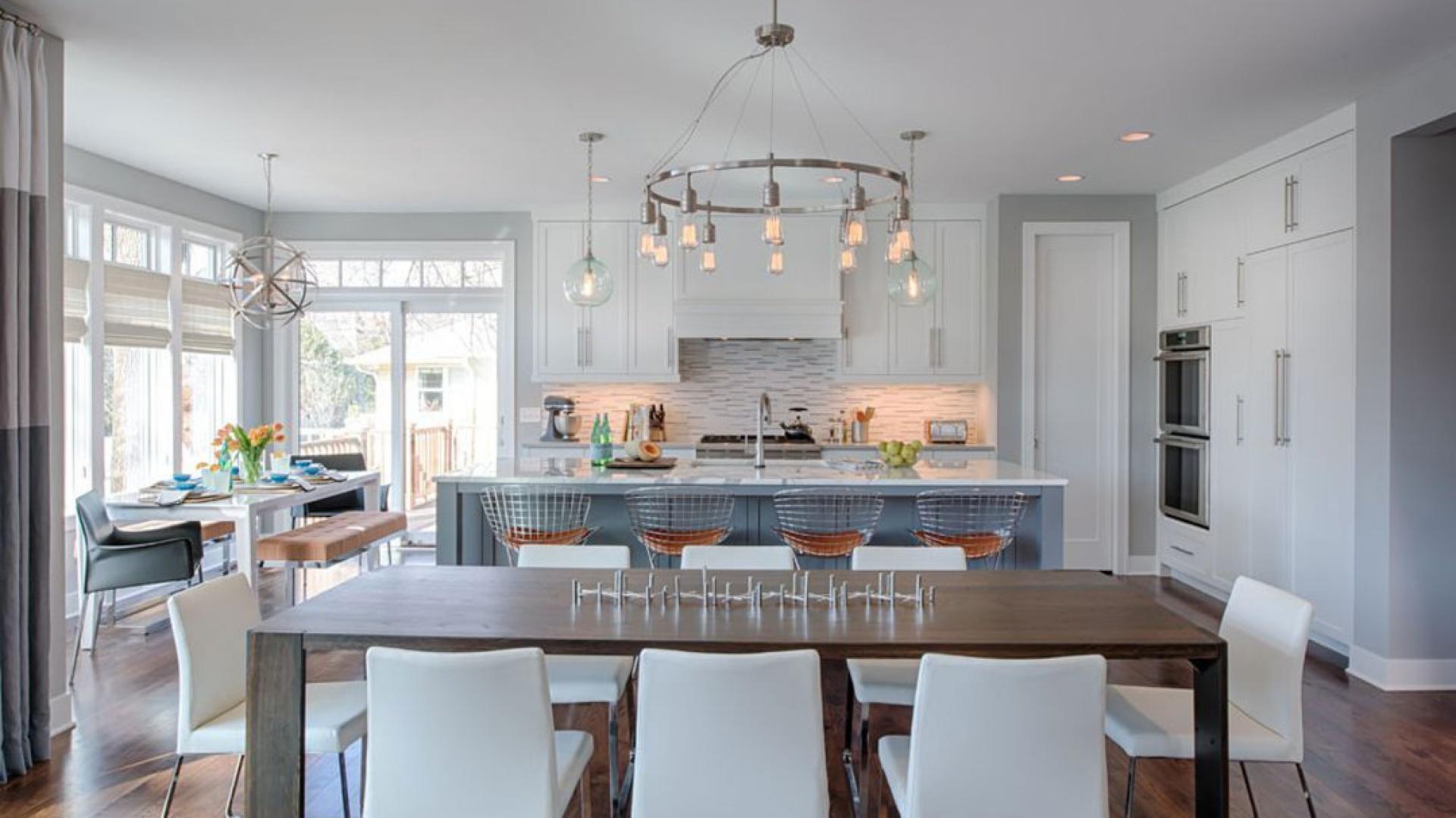 Duża kuchnia, połączona z okazałą jadalnią mieści w sobie mieszankę różnych stylów. Metalowe krzesła przywodzą na myśl industrialne klimaty, podczas gdy okazały żyrandol nad stołem nawiązuje do stylistyki glamour. Z kolei lampy zawieszone nad wyspą kuchenną utrzymane są w vintage'owym stylu. Fot. Refined.