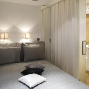 Niewielka sypialnia została wydzielona z przestrzeni mieszkania za pomocą szklanych, przesuwnych drzwi. Projekt: Monika i Adam Bronikowscy. Fot. Bartosz Jarosz.