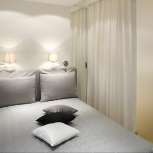 Sypialnię powiększono optycznie za pomocą wąskich, wysokich luster umieszczonych po obu stronach łóżka. Projekt: Monika i Adam Bronikowscy. Fot. Bartosz Jarosz.