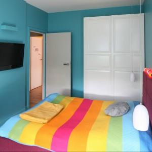 W niewielkiej sypialni turkus stał się barwą przewodnią. Kolorowe ściany dopełnia tapicerka łóżka oraz biała, pojemna szafa. Projekt: Luiza Jodłowska. Fot. Bartosz Jarosz.
