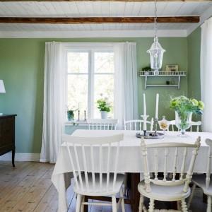 Sąsiadująca z kuchnią jadalnia jest na tyle przestronna, że wykończenie jej w ciemniejszych barwach nie przytłoczyło wizualnie wnętrza. Stonowany odcień pastelowej zieleni tworzy elegancką kompozycję z mahoniową komodą i białym sufitem, na którym wyeksponowano ciemniejsze belki stropowe. Fot. Stadshem.