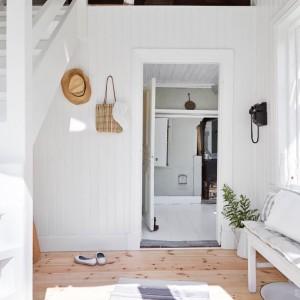 Na poddasze prowadzą białe drewniane schody. Brak zamkniętej klatki schodowej sprawił, że zyskano więcej przestrzeni w holu. Fot. Stadshem.