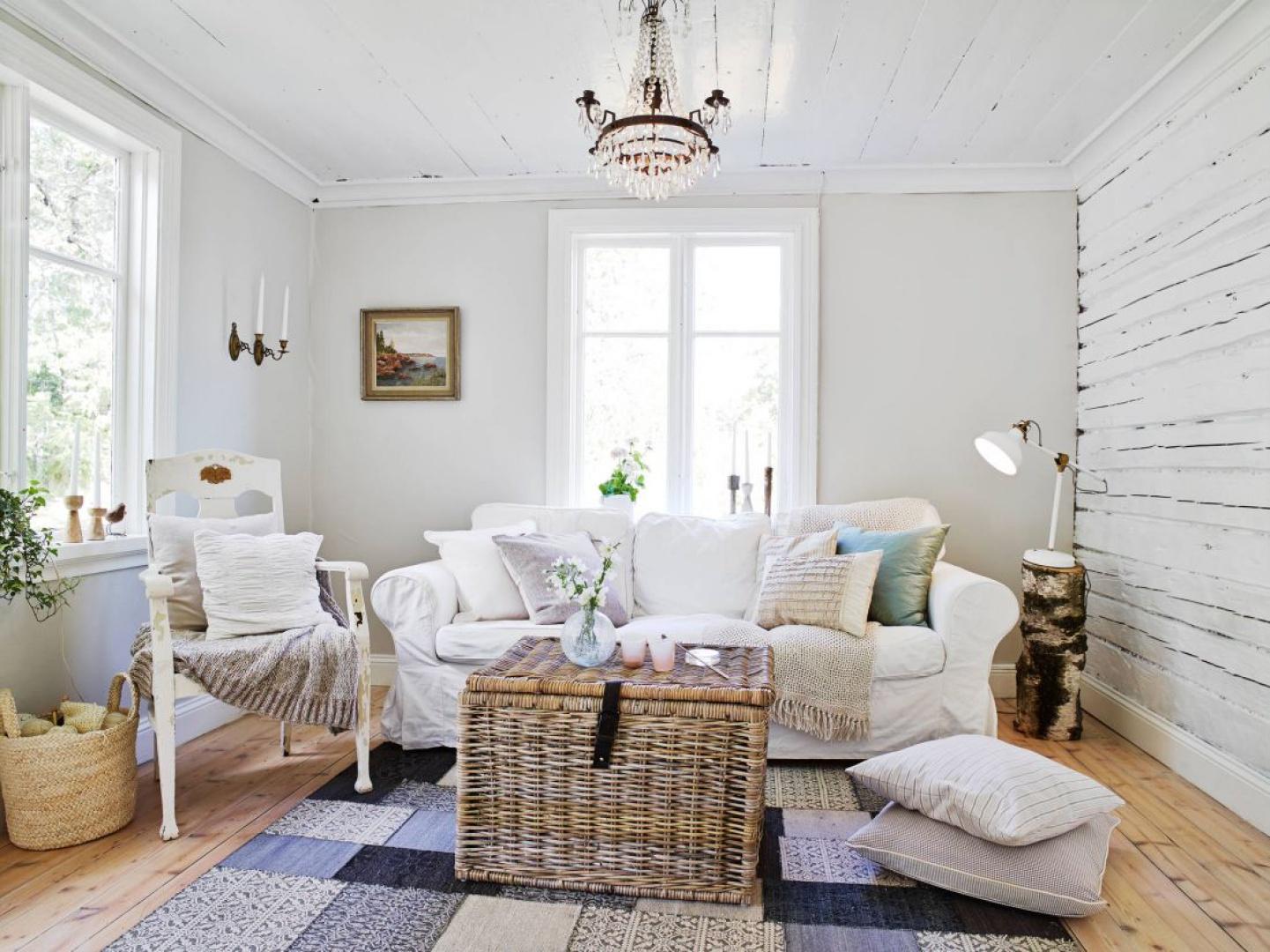 Urokliwy salon urządzono z naciskiem na rustykalny charakter wnętrza. Kreatywnie potraktowano meble: podstawkę pod nocną lampkę wykonano z drewnianego pieńka, a funkcję stolika pełni wiklinowy kufer. Fot. Stadshem.