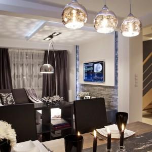 Przykuwającym wzrok elementem dekoracyjnym w salonie są lampy w pięknych, szklanych oprawach nad stołem oraz duża stojąca lampa ze stalowym kloszem, pochylająca się nad ławą. Fot. Małgorzata Brewczyńska.