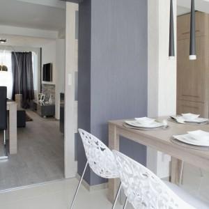 Do kuchennego stołu dobrano białe ażurowe meble, które swoją formą nadają przestrzeni lekkości. Neutralna kolorystyka sprawia, że komponują się wizualnie zarówno z drewnianym stołem jak i widocznym otwartym salonem. Fot. Małgorzata Brewczyńska.