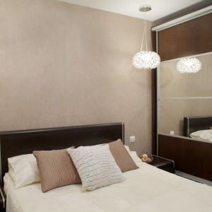 Sypialnię urządzono w ciepłych kolorach: beżach i czekoladowych brązach. Pomieszczenie optycznie powiększa duże lustro na przesuwnych drzwiach wysokiej szafy, które jednocześnie dzięki sposobie otwierania nie zabierają przestrzeni przy ich codziennym użytkowaniu. Fot. Małgorzata Brewczyńska.