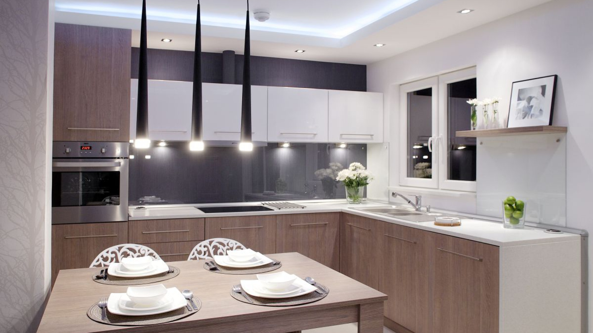 Aranżacja kuchni to przede wszystkim jasne barwy. Biały kolor na ścianach, blatach i frontach podwieszanych szafek optycznie powiększa przestrzeń. Szafki i ściana nad zlewozmywakiem zostały wykończone na połysk, zapewniając refleksy światła, dodatkowo stwarzające iluzję większego pomieszczenia. Fot. Małgorzata Brewczyńska.