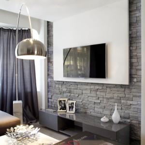 Ściankę działową pomiędzy salonem a holem wykończono eleganckim naturalnym łupkiem kamiennym. Futurystycznym nowoczesnym akcentem jest podwieszany sufit, łączący się z płytą gipsową pokrywającą fragment ścianki. Fot. Małgorzata Brewczyńska.