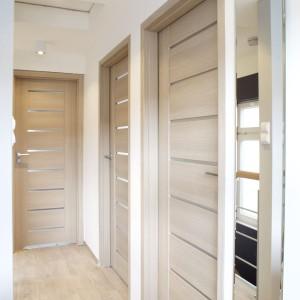 Drzwi wewnętrzne do wszystkich pomieszczeń utrzymano w jednakowej stylistyce. Kolorystycznie zostały dopasowane do podłóg. Ciepłe, jasne barwy drewna ocieplają delikatnie przestrzeń, ale nie pomniejszają jej optycznie. Fot. Małgorzata Brewczyńska.