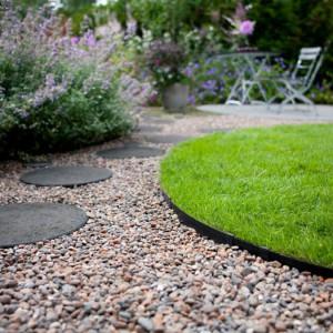 Okrągłe płyty betonowe doskonale prezentują się na tle żwirowej nawierzchni. Połączenie różnych struktur tworzy ciekawy efekt.  Fot. Kekkila.