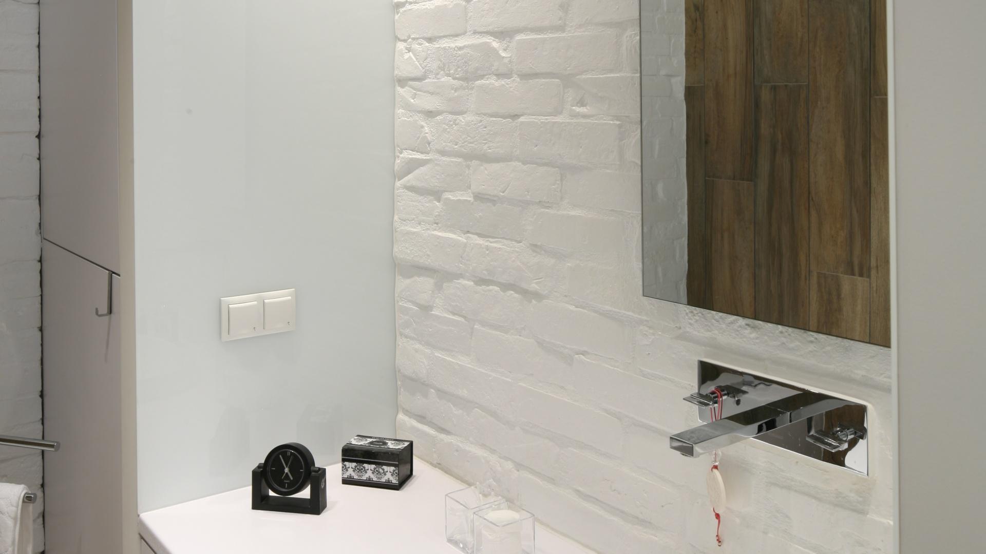Projekt zabudowy meblowej z białego lakierowanego MDF-u uwzględnia szafki, głęboką szufladę pod umywalką oraz wysoką szafę, wktórej zabudowano pralkę ielementy łazienkowej instalacji. Bok szafy oraz taki sam fragment płyty po drugiej stronie  zabudowy tworzy efektowne obramowanie. Fot. Bartosz Jarosz