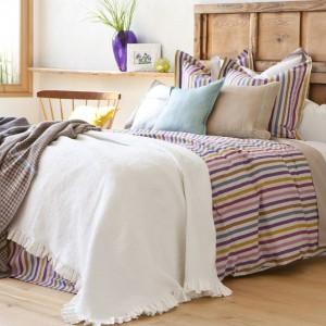 Za pomocą tkanin w szybki i łatwy sposób możemy wprowadzić kolor do wnętrza. Na zdjęciu pasiasta narzuta z tkaniny żakardowej i poszewka na poduszkę dekoracyjną. Fot. Zara Home.
