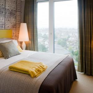 Stonowaną sypialnię urozmaicają żółte, energetyczne dodatki. The Filaments Hotel.