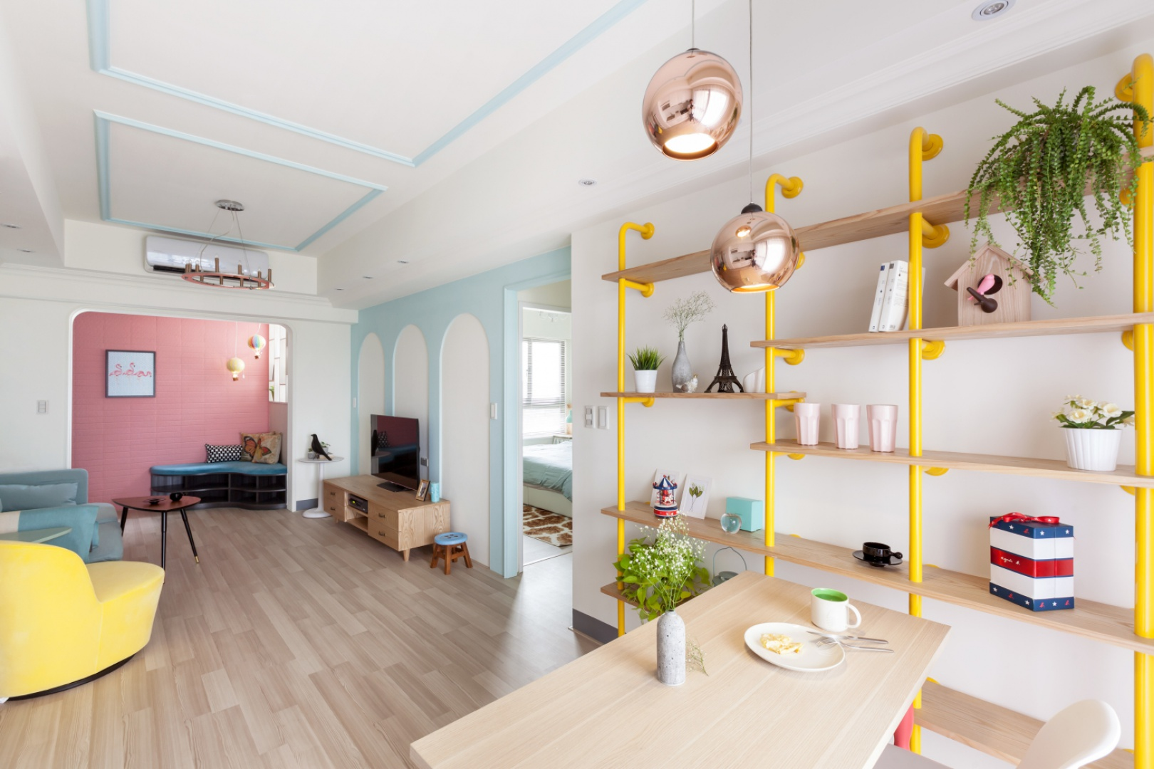 Drewniane elementy umeblowania to w znacznej mierze proste formy, pozbawione zbędnych ornamentów. Kontrastują z fantazyjnymi kształtami kolorowego wyposażenia mieszkania i stanowią wizualną równowagę. Projekt: HAO Design Studio. Fot. Hey! Cheese.