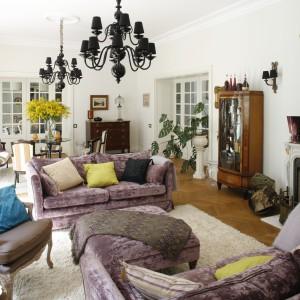 W przestronnym salonie miejsce dla siebie znalazł zestaw wypoczynkowy w stylu angielskim, wykonany na zamówienie i obity angielskimi tkaninami. Ich ciepłe, jasno fioletowe wybarwienie podkreśla przytulna atmosferę całego wnętrza. Projekt właściciele. Fot. Bartosz Jarosz.