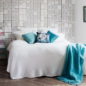 Turkusowa narzuta, poduszka oraz stolik nocny w zestawieniu z jasną ścianą i drewnianą podłogą tworzą spójną kompozycję. Fot. Mr Perswall.
