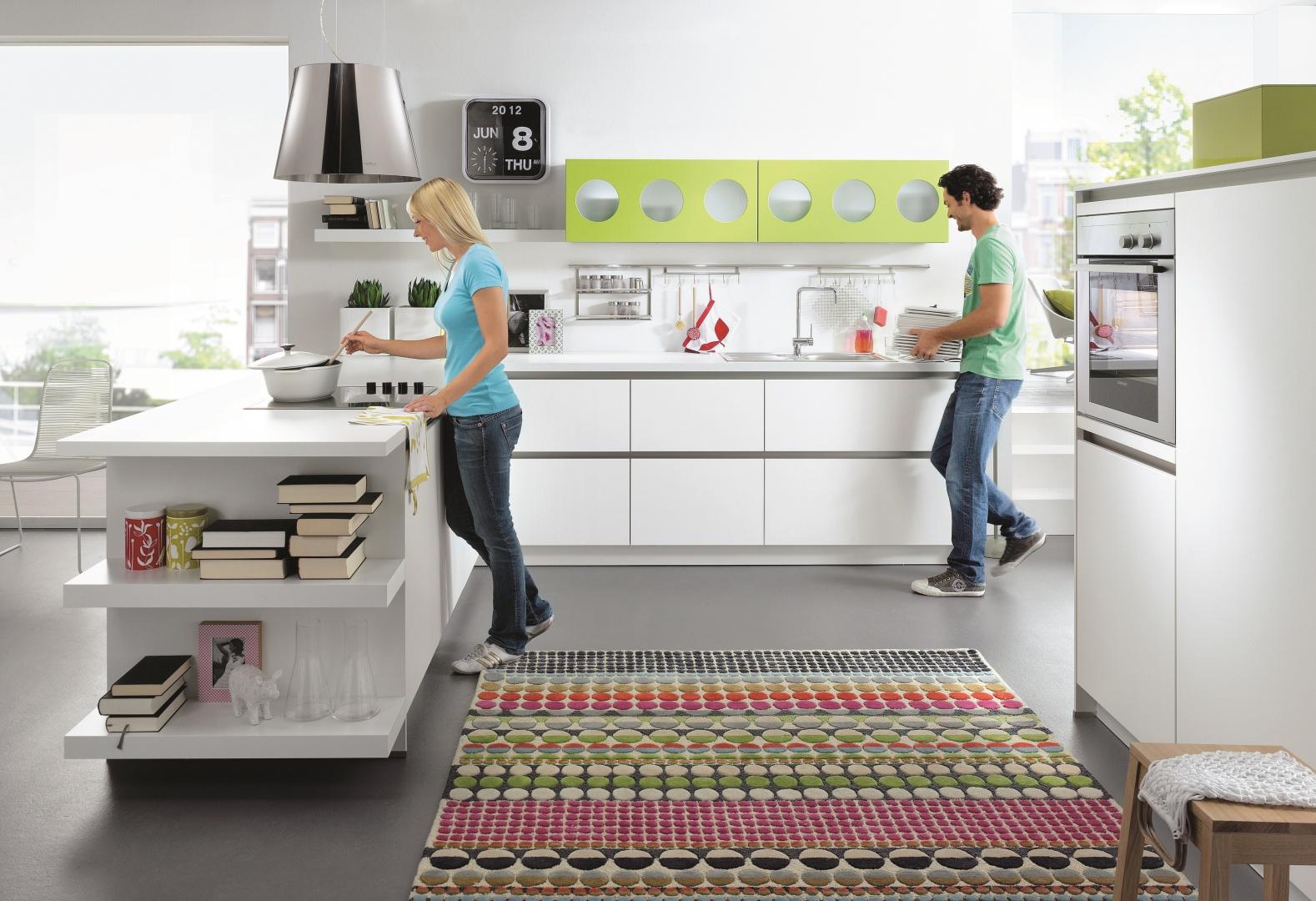 Białe fronty mebli ożywiają szafki wiszące w intensywnym, zielonym kolorem z oryginalnym wzorem. Takie zestawienie prezentuje się lekko i świeżo. Meble kuchenne Biella zprogramu Start firmy Schüller. Fot. Schüller.