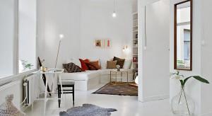 Mieszkanie z jednym pokojem niemal w całości pomalowano na biało. Białą farbą pokryto podłogi, ściany i sufity. Powstałe sterylne wnętrze ocieplają tekstylia, drewniane akcenty i zabytkowe sztukaterie.