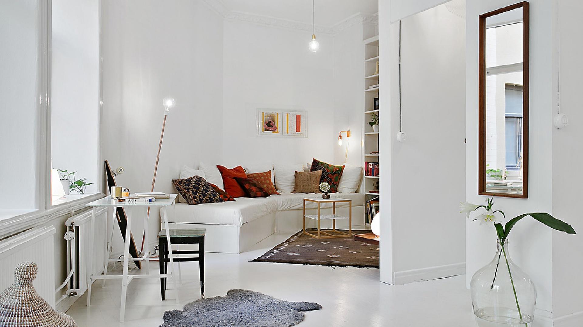 Ściany, podłogi i sufit pomalowano na biały kolor. Wszechobecną biel ocieplają przytulne tekstylia: włochaty dywanik i liczne poduszki w ciepłych jesiennych barwach. Fot. Alvhem Makleri.