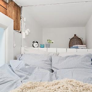 Urokliwa, niewielka sypialnia z praktyczną półką za zagłówkiem łóżka tworzy przytulną przestrzeń do wypoczynku i spania. Fot. Alvhem Makleri