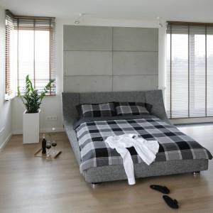Na ścianie za łóżkiem umieszczono betonowe płyty o równych rozmiarach. Wprowadzają one industrialny charakter do wnętrza. Projekt:  Agnieszka Ludwinowska. Fot. Bartosz Jarosz.