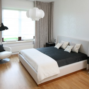 Ścianę za łóżkiem udekorowano delikatną, jasną tapetą, która dodaje wnętrzu elegancji. Stanowi ona doskonałe tło dla czarnej, wiszącej lampy oraz stolików nocnych. Projekt: Katarzyna Koszałka. Fot. Bartosz Jarosz.