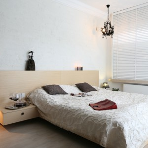 Jasna ściana w jednolitym kolorze stanowi przyjemne tło dla drewnianego łózka z wysokim zagłówkiem. Przestronną sypialnię ożywiono ciemnymi dodatkami w stylu glamour. Projekt: Monika Włodarczyk, Jarosław Jończyk. Fot. Bartosz Jarosz.
