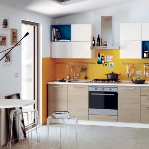 Meble z kolekcji Urban firmy Scavolini. To propozycja do niedużej kuchni. W roli malutkiego, praktycznego stolika sprawdził się poszerzony blat jednej z szafek. Proste w formie meble ożywiają szafki w biało-niebieskiej kolorystyce oraz żółta ściana na nad blatem.