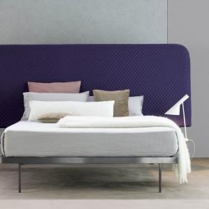Łóżko Contrast z wysokim, tapicerowanym zagłówkiem o oryginalnym , lekko zaokrąglonym kształcie. Fot. Bonaldo.