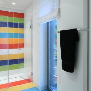 Bezprogowe wejście do  wnęki kąpielowej oraz  odpływ liniowy wposadzce zamiast brodzika umożliwiły zaprojektowanie kolorowego wzoru okładziny na powierzchni całej podłogi. Kolory zmieniają się wmiarę  zbliżania do prysznica. Fot. Bartosz Jarosz.