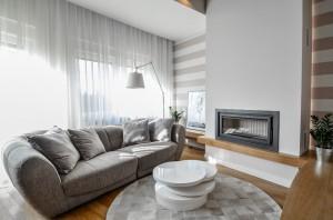 Salon w apartamencie 4-poziomowym. Naturalna kolorystyka i nietypowa przestrzeń tworzą wnętrze przestronne i jasne, a użyte dodatki nadają mu nowoczesny charakter. Szara sofa z kominkiem i telewizorem tworzą zakątek do wypoczynku. Salon płynnie łączy się z aneksem kuchennym.