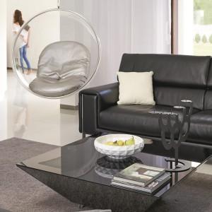 Czarny elegancki komplet wypoczynkowy z kontrastującymi białymi poduszkami, czarna futurystyczna ława oraz szary puchaty dywan nadają wnętrzu eleganckiego wyrazu. Fot. Łukasz Kozyra.