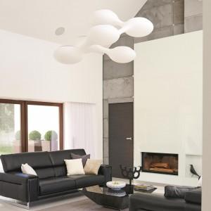 Na salonem powieszono białą, kosmiczną lampę o niebanalnym kształcie. Stanowi ona designerski, futurystyczny akcent we wnętrzu, w którym króluje minimalizm. Fot. Łukasz Kozyra.