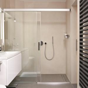 Łazienkę utrzymano w stonowanych kolorach szarości, które ożywają dzięki ceramice łazienkowej w klasycznym białym kolorze. Na ścianie zlokalizowano czarny, przykuwający wzrok grzejnik drabinkowy. Fot. Łukasz Kozyra.