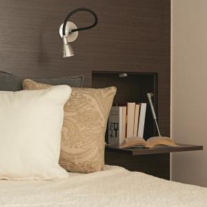 W sypialni panuje bardziej przytulna atmosfera. Zamiast szarości i bieli, dominującymi kolorami są ciepłe beże i brązy. Wzorzyste tekstylia wprowadzają do pomieszczenia domowy, intymny klimat. Na uwagę zasługuje praktyczna półka, która może jednocześnie pełnić funkcję drzwiczek, skrywających niewielką podręczną biblioteczkę, schowaną w szafie. Fot. Łukasz Kozyra.