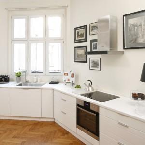 Ścianę nad blatem wykorzystano w tej kuchnie mniej typowo. Zrezygnowano z szafek wiszących, a ich miejsce zajęły z czarno-białe zdjęcia. Przestrzeń zyskała dzięki temu oryginalny, ale i bardziej salonowy charakter. Projekt: Iwona Kurkowska. Fot. Bartosz Jarosz.