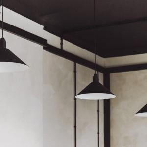 Industrialny styl pomieszczenia podkreślają zwisające z sufitu lampy, pochodzące z opuszczonej części budynku. Rozmieszczone w całym apartamencie, stanowią główne źródło oświetlenia. Fot. Paulina Sasinowska, Maciej Kurkowski, Maciej Sutuła.