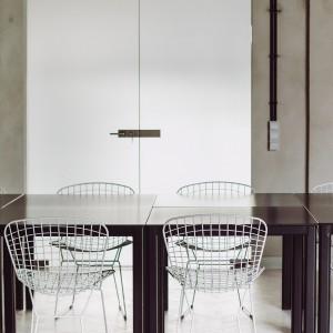 Krzesła wykonane z metalowej siatki podkreślają industrialny charakter wnętrza. Z kolei ich biały kolor komponuje się z podłogą i wprowadza lżejszy klimat do pomieszczenia. Fot. Paulina Sasinowska, Maciej Kurkowski, Maciej Sutuła.