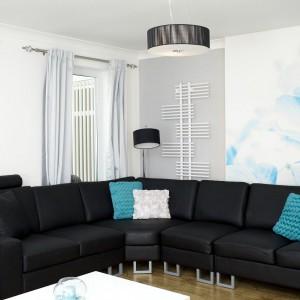 Czarny komplet wypoczynkowy z dużą narożną kanapą stanowią punkt główny salonu. Dominującą czerń ożywiają białe i turkusowe akcenty w postaci przytulnych poduszek i wielkoformatowego obrazu na ścianie. Fot. Małgorzata Brewczyńska.