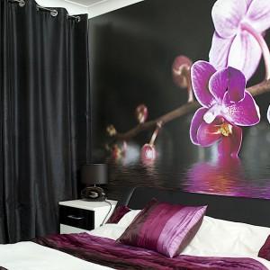 Po obu stronach łóżka postawiono nocne szafki o prostej formie i monochromatycznych kolorach czerni i bieli. Na nich zlokalizowano całkowicie czarne lampki nocne. Całość tworzy elegancki akcent dekoracyjny. Fot. Małgorzata Brewczyńska.