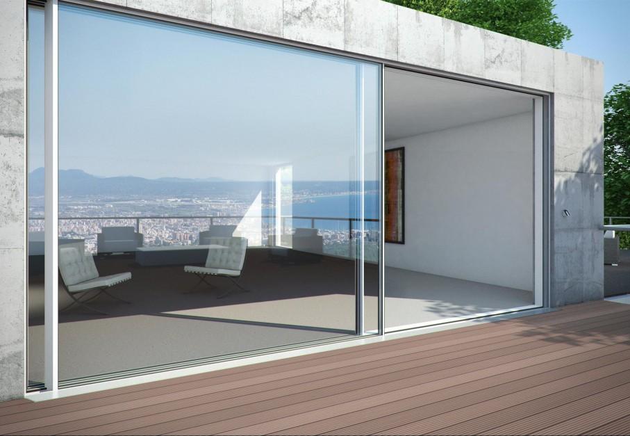Przesuwne, panoramiczne drzwi to propozycja od marki Schüco. Szyby w aluminiowych drzwiach przesuwnych wstawiono w wąskie profile skrzydeł. Nowoczesny system bez uchwytów,klamek zapewnia minimalistyczny wygląd.  Fot. Schüco.