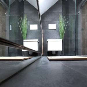 Łazienkę utrzymano w grafitowym kolorze, na którego tle wybija się biała ceramika o kanciastych formach. Z surową stylistyką komponują się szklana, prosta obudowa kabiny prysznicowej oraz lustrzana tafla, którą obłożono wannę. Przeszklenia i lustra dodatkowo wizualnie powiększają przestrzeń. Fot. Vostok Design.