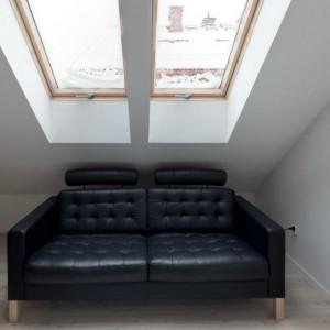 Pod oknami w salonie zlokalizowano czarną, dwuosobową stylową sofę. Głębokie wnęki okienne pozwalają na swobodny wypoczynek w pozycji siedzącej. Fot. Vostok Design.