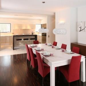 Nowoczesny, biały stół uzupełniają czerwone krzesła w nieco klasycznej formie tworząc tym samym oryginalną i kolorową jadalnię. Projekt: Małgorzata Szajbel-Żukowska. Fot. Bartosz Jarosz.