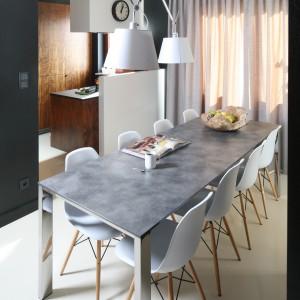 Minimalistyczny stół w modnym, szarym kolorze uzupełniają białe krzesła w subtelnym kształcie. Projekt: Michał Dudko. Fot. Bartosz Jarosz.