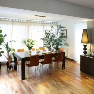 Stół i osiem krzeseł, ustawione na końcu salonu tworzą nowoczesną i wygodną jadalnię odpowiednią dla dużej rodziny oraz do przyjmowania gości. Projekt: Marcin Lewandowicz. Fot. Bartosz Jarosz.