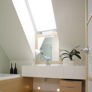 Umieszczona pod oknem umywalka została obudowana materiałem typu solid surface. Wraz z blatem tworzy prostą geometryczną bryłę, która idealnie pasuje do tego wnętrza. Fot. Bartosz Jarosz.