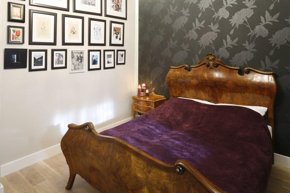 Jasna ściana przyjemnie kontrastuje z ciemną tapetą. Umieszczono na niej zdjęcia w czarnych ramkach, które tworzą dynamiczną kompozycję. Projekt: Monika Gorlikowska. Fot. Bartosz Jarosz.